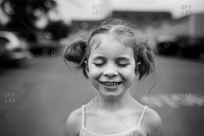 Portrait of a smiling freckle-faced girl with her eyes closed