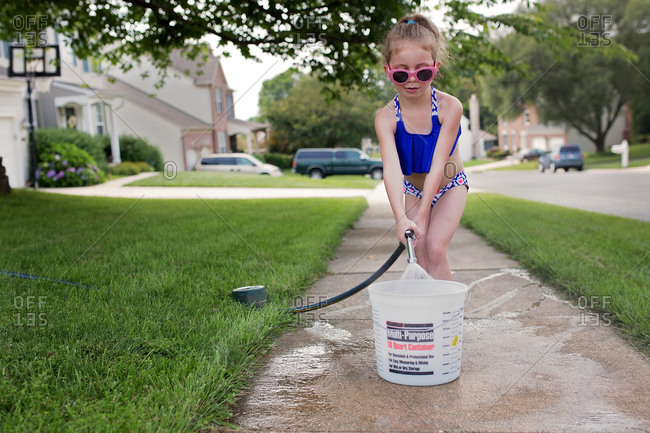 Young girl in sunglasses filling a bucket with hose on sidewalk