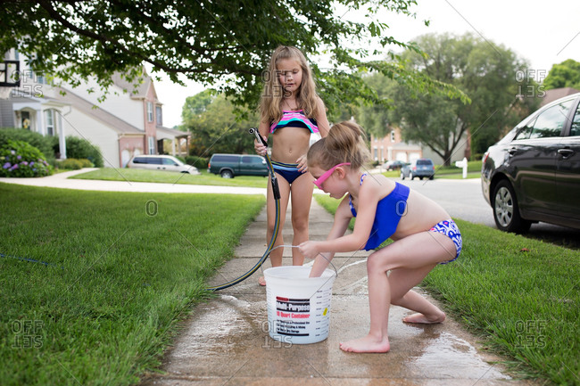 Two girls with a bucket and hose on sidewalk