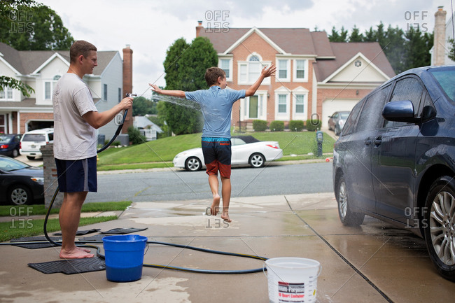 Boy running through water while his dad hoses off the car