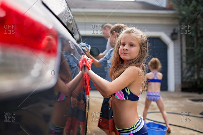 Girl washes car in driveway with her siblings and father