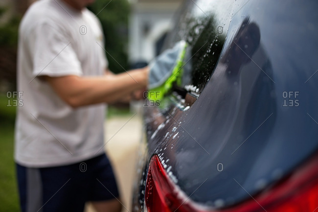 Close-up of car being washed by adult man