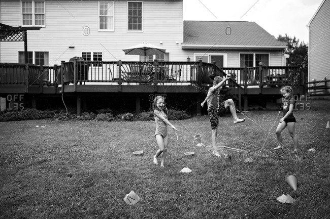 Three children play in backyard sprinkler