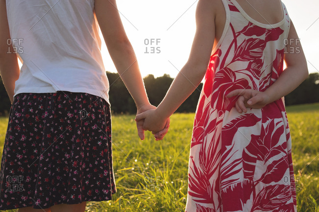 Back view of two young girls holding hands at sunset