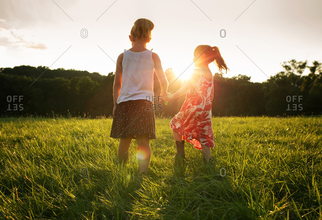 Two young girls walk through grass holding hands at sunset