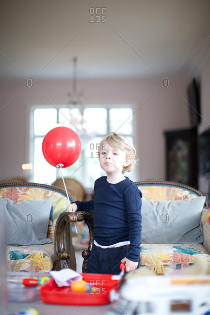 Cute boy with plastic ball at home