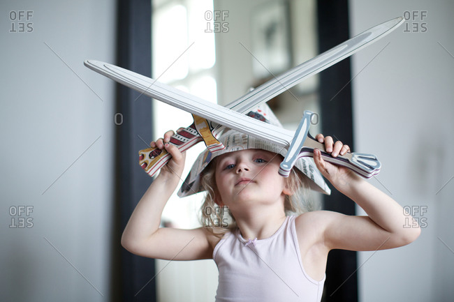 Girl wearing paper hat and holding sword