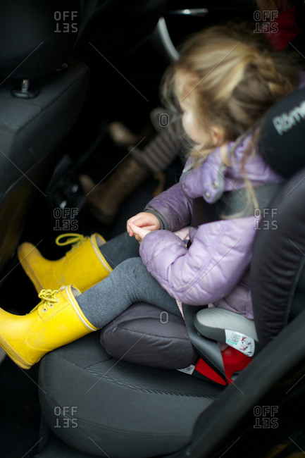 Little girl strapped into child seat
