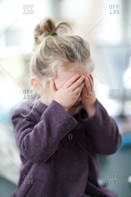 Small girl covering eyes with hands hide and seek