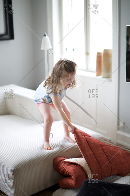 Small girl pulling mattress in living