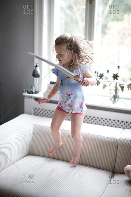 Small girl jumping on sofa