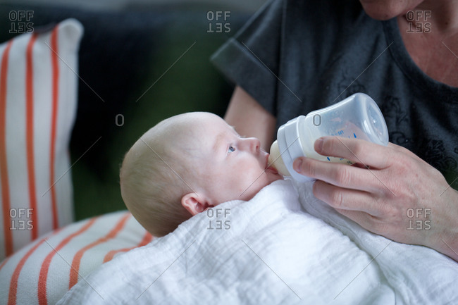 Mother's hand giving a baby a bottle