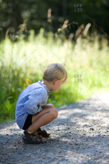 Boy looking with curiosity at gravel road