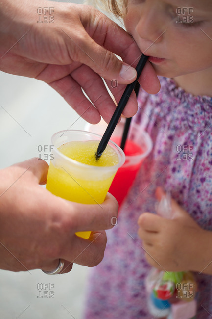 Parent helping daughter to drink slush ice