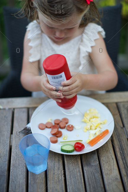 Girl squeezing ketchup out of bottle