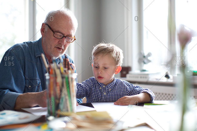 Grandfather helping grandson with homework