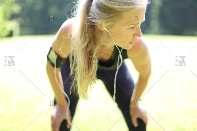 Blonde woman bending in jogging outfit with earphones