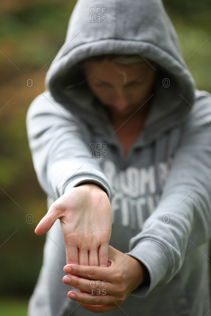 Sporty woman in grey hoodie stretching her hands and wrists