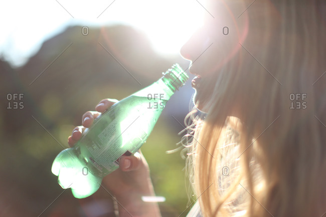 Young woman in soft sunlight drinking from bottle of  mineral water