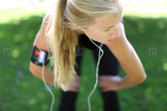 Woman in jogging outfit and earphones catching her breath