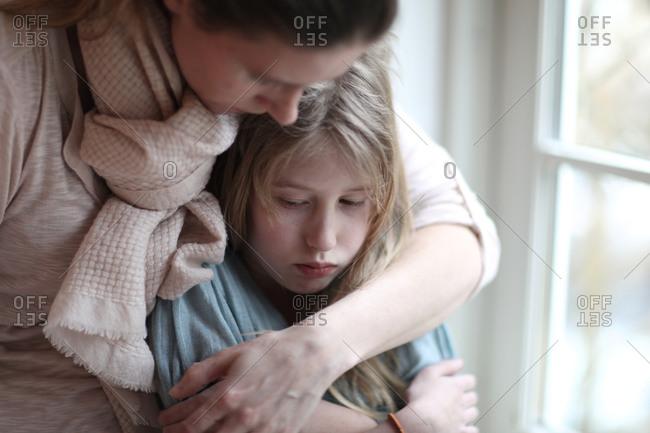 Sad and angry pre teen girl and mother