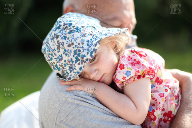 Cute toddler girl with liberty summer hat hugs grandfather