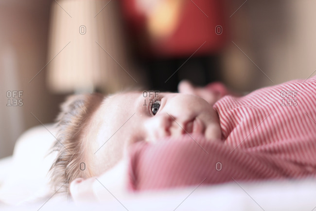 Newborn baby with hair in red and white body stocking lying on changing mat