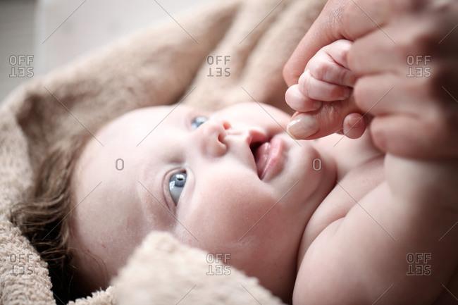 Baby grasping parent's finger