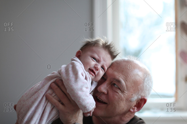 Grandfather holding crying baby