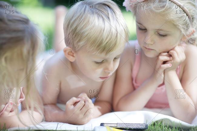 Cute little kids looking at smartphone children