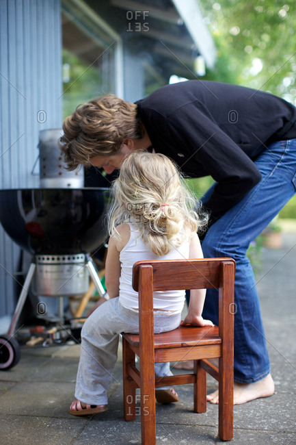 Girl with father looking at grill chimney starter father and child