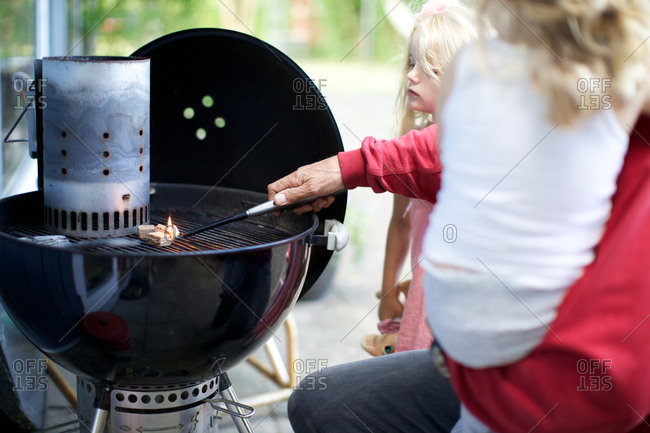 Father and daughter with fire starter blocks on grill