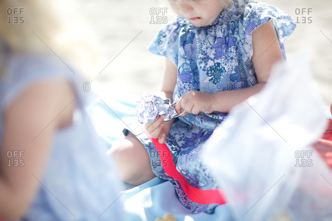 Little girl opening a chocolate wrapper at beach