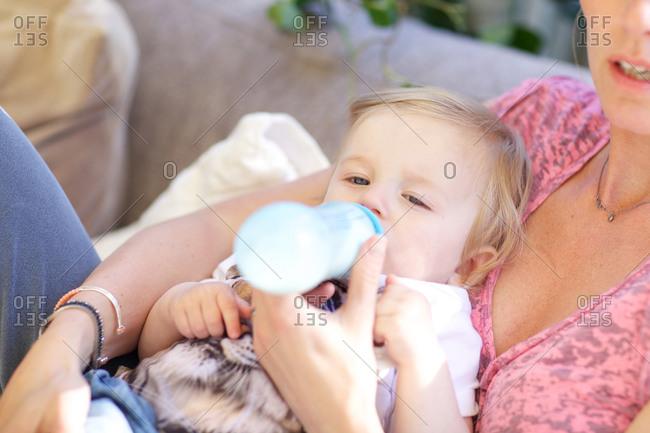 Mother feeding bottle milk to her child