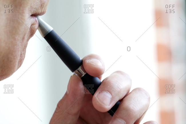 Smoker inhaling nicotine from e-cigarette