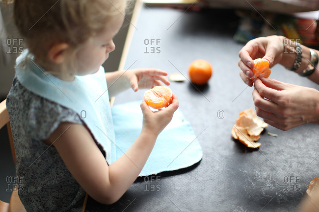 Small girl eating clementine at kindergarten table