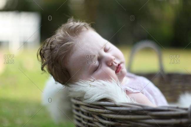 Baby girl sitting sleeping on sheepskin in garden basket