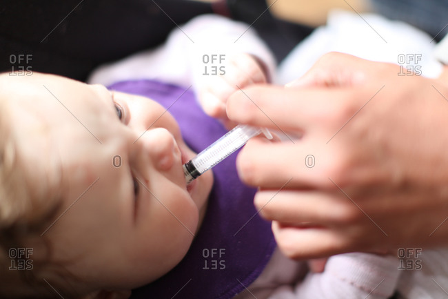 Baby given medicine orally from syringe