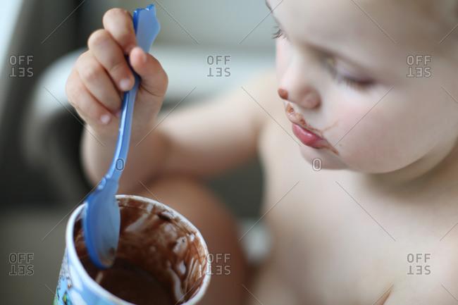 Toddler girl with a carton of chocolate ice cream