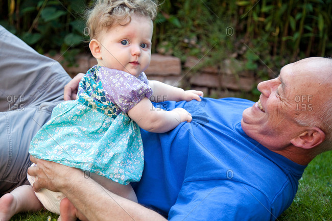 Baby girl and grandfather playing on lawn