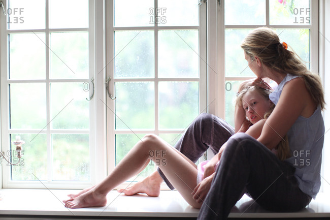 Mother and young teenage daughter in summer dress sitting on windowsill