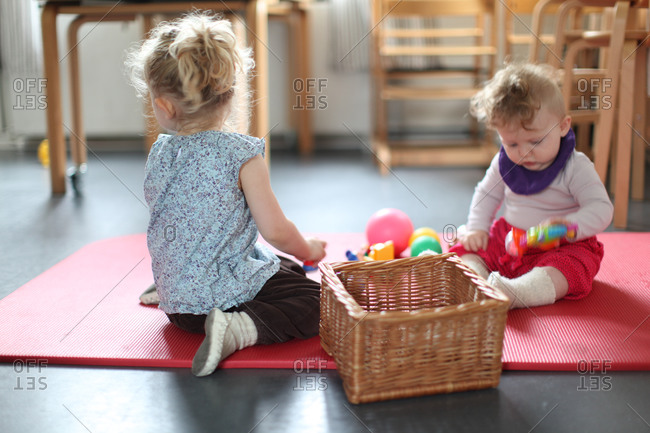 Toddler girl and baby girl playing with toys on red floor mat in kindergarten