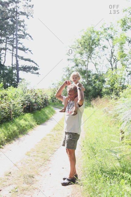 Man carrying small girl on shoulder on country lane stock