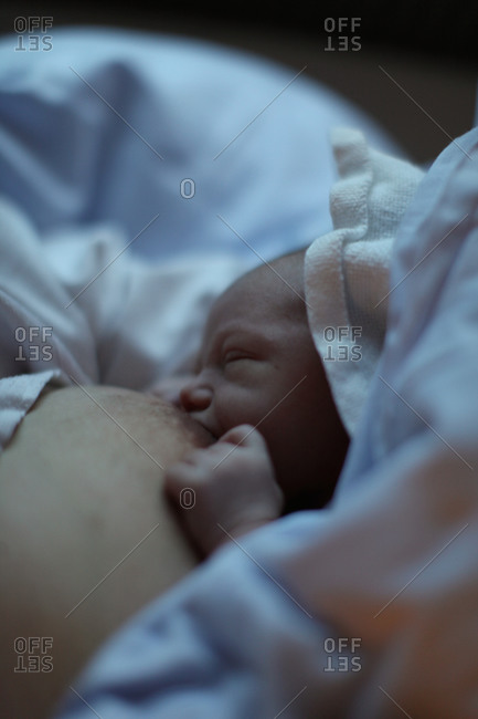 Newborn baby being fed by her mother