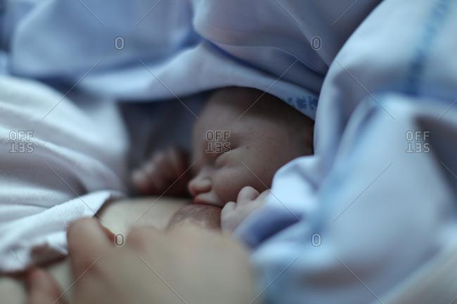 Newborn baby feeding at mother's breast