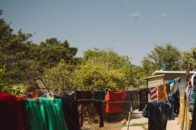 Laundry hanging on a clothesline strung across a backyard