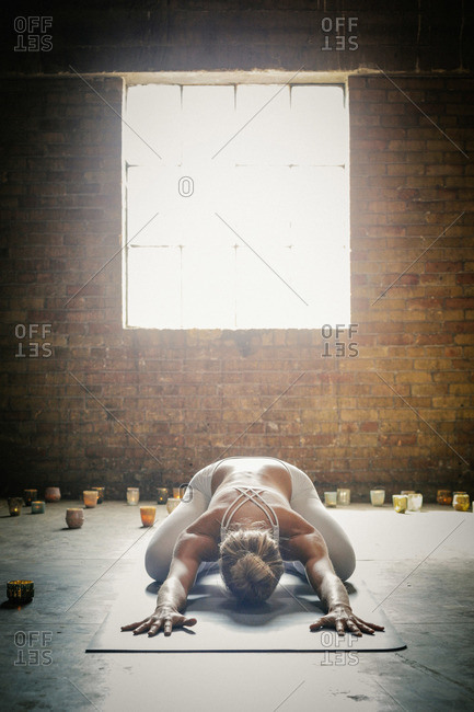 A blonde woman in a white crop top and leggings, bending down on a yoga mat surrounded by candles, doing yoga