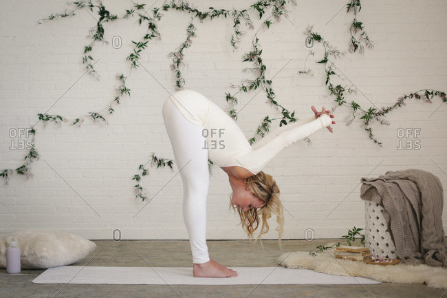 A blonde woman in a white leotard and leggings bending down, stretching A creeper plant on the wall behind her