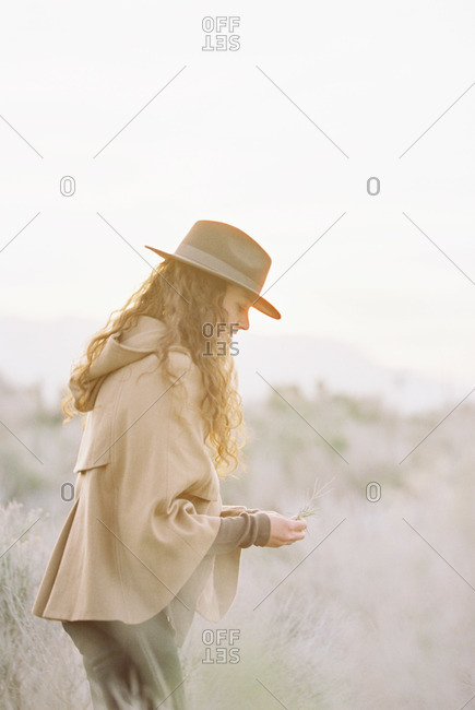 A woman in a warm coat and a hat picking wild flowers