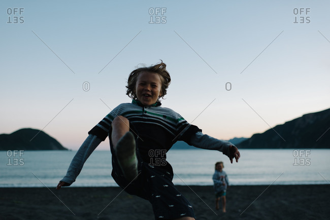 Boy jumping on beach at twilight